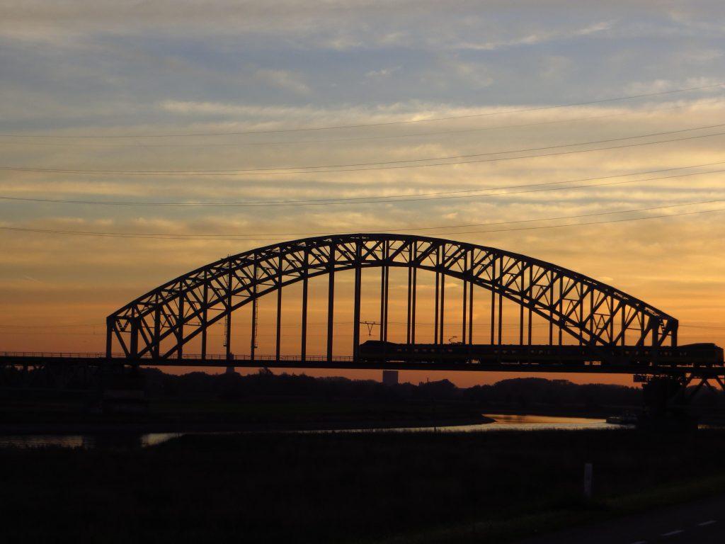 Als ik de spoorbrug tussen Arnhem en Nijmegen passeer is de zon juist opgekomen.